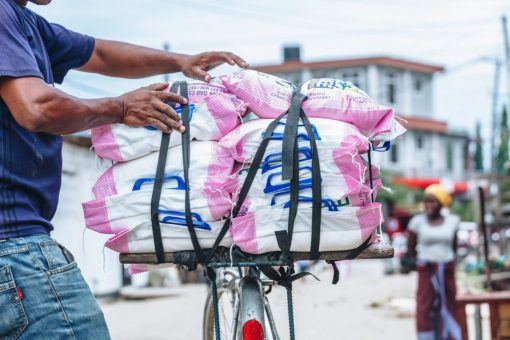 photo of man with bike with stacks of flour bags